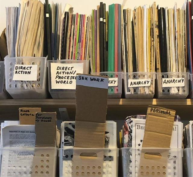 Shelves at the Incendium Radical Library, including works sorted in topics such as Direct Action, Anarchy, and Sex Work.