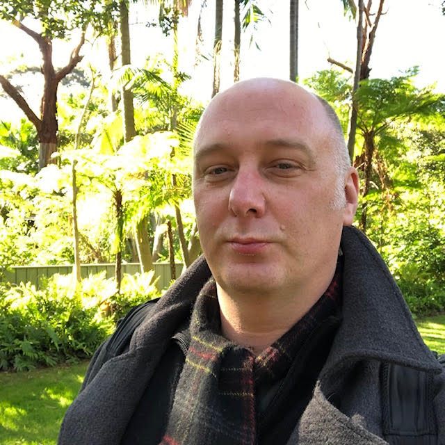 Me at Adelaide Zoo - a bald man with a tartan scarf, looking a bit tired, but with some nice trees in the background.